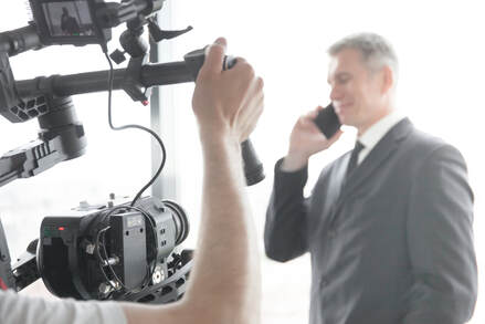Picture of a video production being done for a corporate image repair infomercial.  Picture shows a cameraman filming an executuve talking on this cellulr phone.
